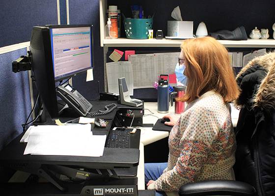 A Shared Ride Dispatcher wears a mask at her work station